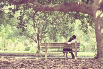 girlfriend boyfriend sitting on outdoor bench