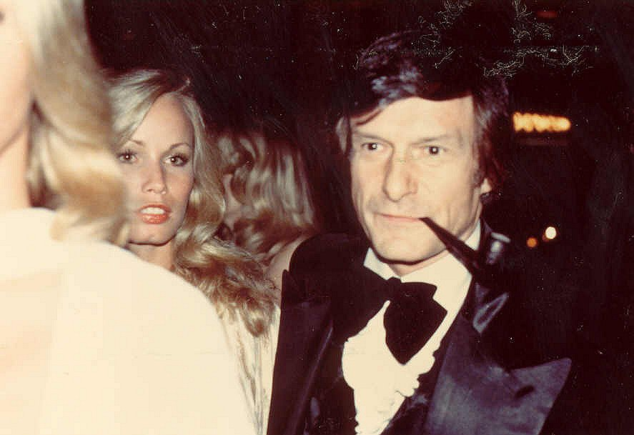 Hugh Hefner in a tuxedo and smoking a pipe