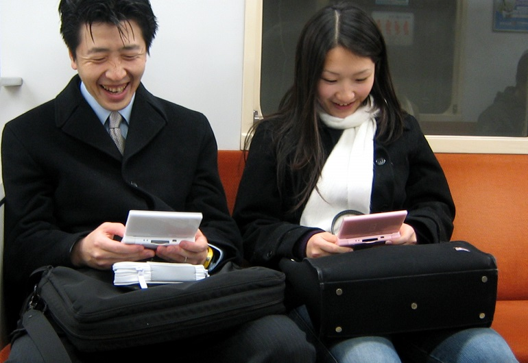 A couple playing games on their Nintendo DS on a train
