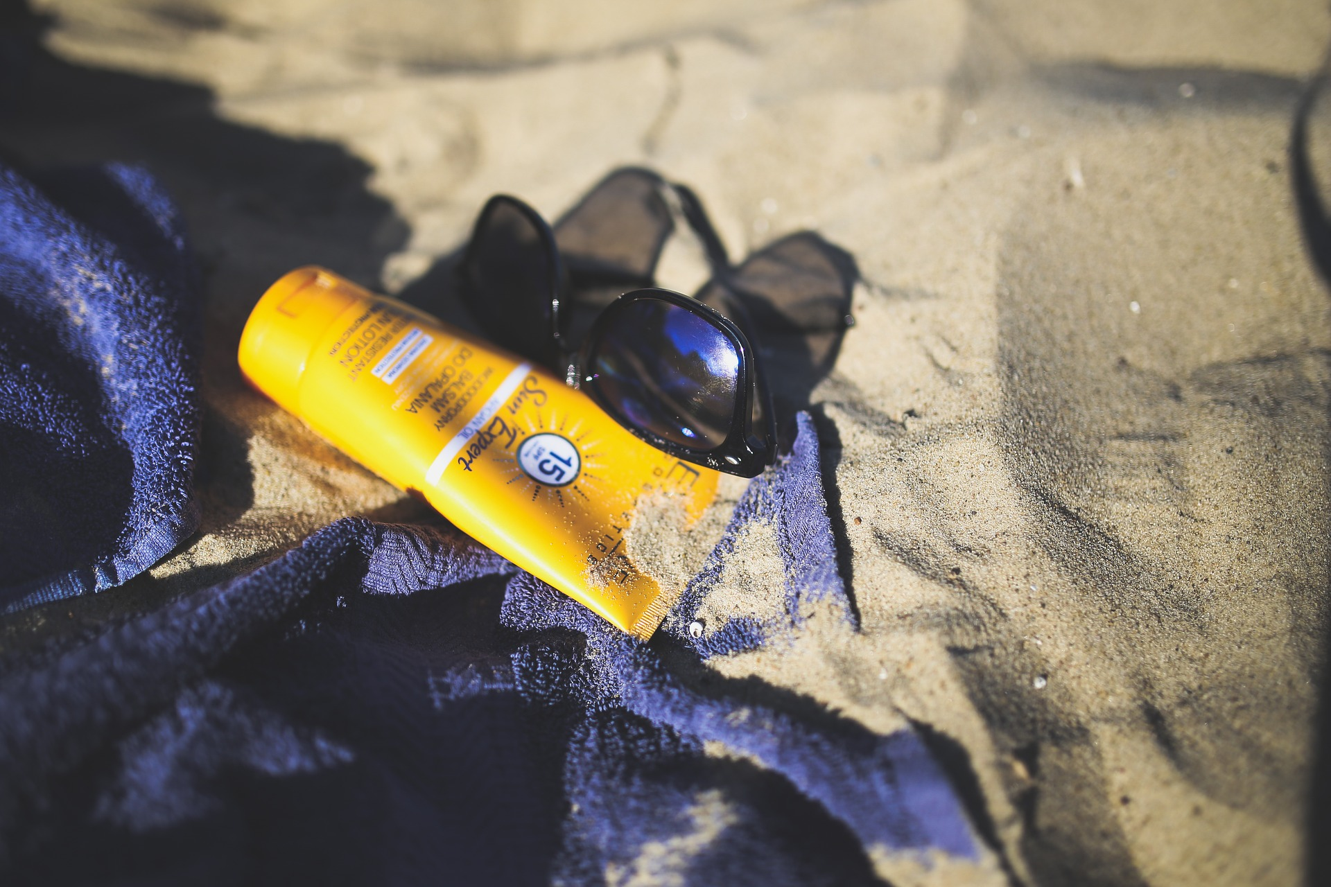 Sunscreen and sunglasses by the beach