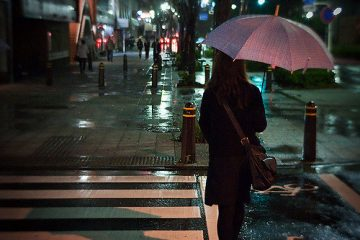 Woman About to Cross the Road While Holding an Umbrella in the Rain