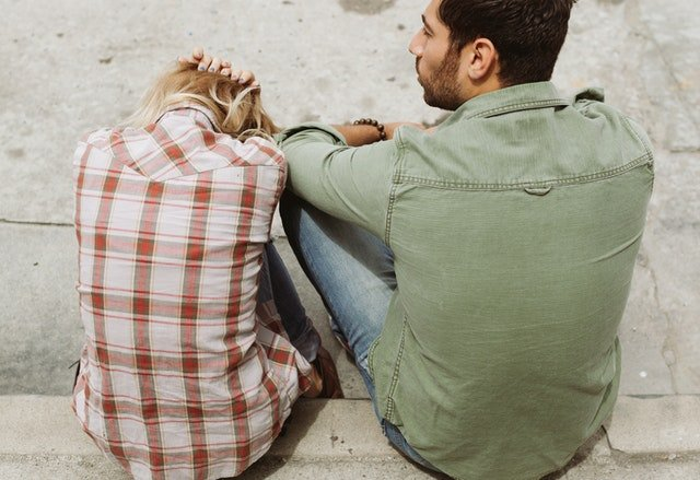 A Couple Sitting On Pavement