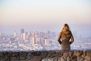 Woman Sitting On A Rock Wall